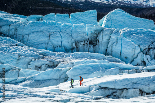 Fényképezés  Two glacier guides walking among large crevasses and seracs on top of the Matanuska Glacier in Alaska