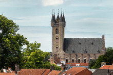 Sluis, The Netherlands -  June 16, 2019: View Over Red Roofs At The Brown Brick Belfry With Clock Tower Under Light Blue Sky. Some Green Foliage.