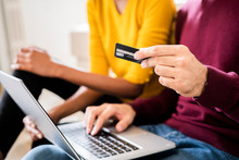 Close-up Of Couple At Home Shopping Online With Laptop And Credit Card