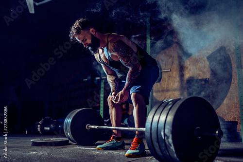 Muscular fitness man preparing to deadlift a barbell over his head in modern fitness center Obraz na płótnie