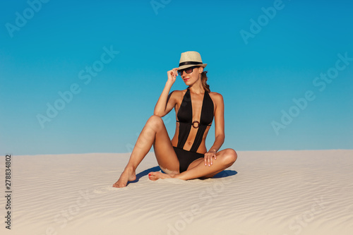 Obraz Portrait of sexy beautiful tanned model woman posing in fashion black swimwear bikini, fedora hat and sunglasses sand desert beach. Exotic country travel and rest concept. Slim figure and sport body. - fototapety do salonu
