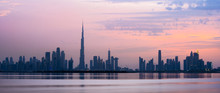 Stunning View Of The Dubai Skyline Silhouette During Sunset With The Magnificent Burj Khalifa And Many Other Buildings And Skyscrapers. Silky Smooth Water Flowing In The Foreground.