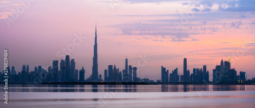 Foto Stunning view of the Dubai skyline silhouette during sunset with the magnificent Burj Khalifa and many other buildings and skyscrapers