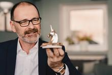 Mature Businessman Holding A Unicorn Figurine