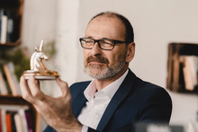 Mature Businessman Holding A Unicorn Figurine