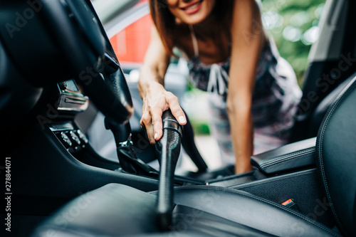 Fototapeta Interior car detailing. Happy middle age woman cleans the interior of her car with vacuum cleaner. obraz