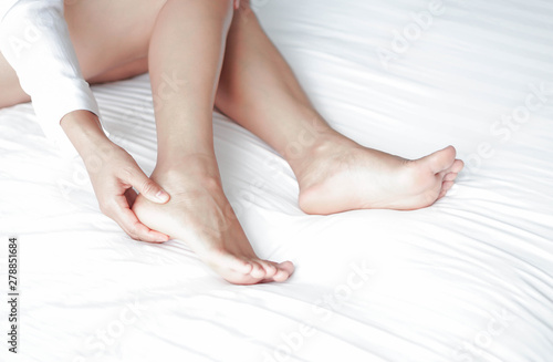 Carta da parati Close up woman touching her heel with pain lying on white bed, health care conce