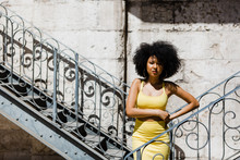 Beautiful African American Woman In Yellow Suit Standing And Leaning In Railing And Looking At Camera On Urban Background
