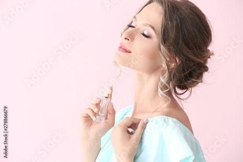 Obraz Beautiful young woman with bottle of perfume on color background - fototapety do salonu