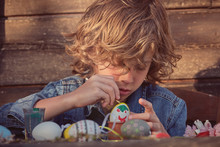 Adorable Child Sitting And Painting Eggs With Bright Color At Wooden Table