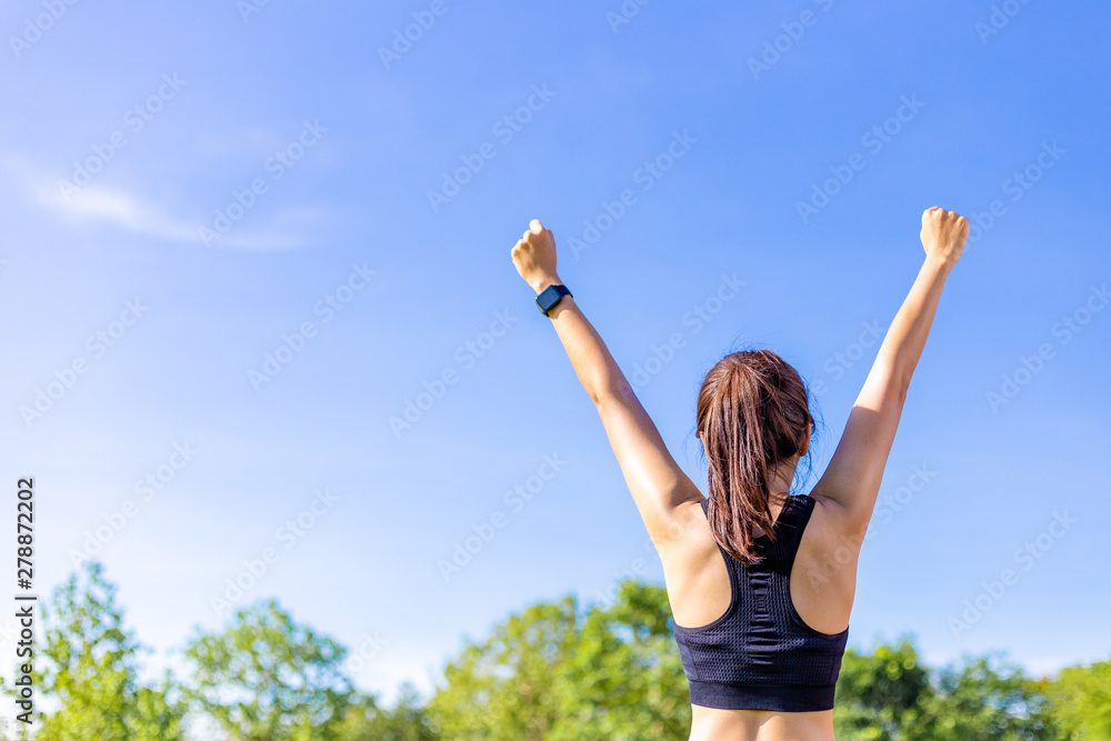 Fototapety, obrazy: Back view of a woman in stretching up her arms happily at an outdoor field with blurred trees and clear blue sky background