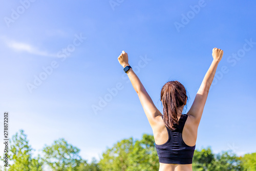 Fotografia  Back view of a woman in stretching up her arms happily at an outdoor field with