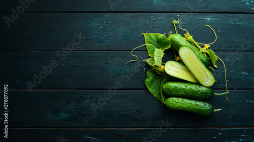 Fototapeta Sliced fresh green cucumbers. On a black background. Top view. Free space for your text. obraz