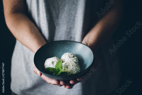 Crop view of anonymous woman holding bowl with stracciatella ice cream balls decorated with mint leaves