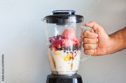 Fototapeta A blender filled with fresh whole fruits for making a smoothie or juice