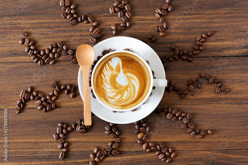 Wall Murals Cafe white coffee cup with latte art and roasted coffee beans around