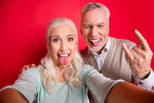 Close Up Photo Beautiful She Her He Him His Aged White Hair Guy Lady Partners Couple Make Take Selfies Funky Tongue Out Mouth Rock Concert Wear Sweater Shirt Waistcoat Isolated Red Burgundy Background