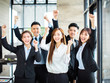 confident asian business team hands up and celebrating