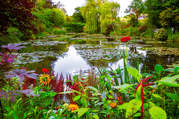 Fototapeta Do jadalni Monet's garden and pond at Giverny, France. Beautiful garden and pond with clustered of colorful flowers, variety of trees and shrubs in summer at Giverny.