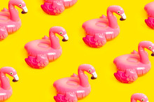 Creative Summer Beach Concept. Pattern From Inflatable Pink Mini Flamingo On Yellow Background, Pool Float Party. Flat Lay, Copy Space. Flamingo Trend Inflatable Toy. Summer Background