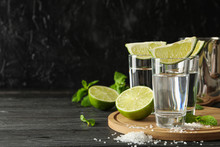 Tequila Shots With Lime Slices, Salt And Mint On Wooden Background