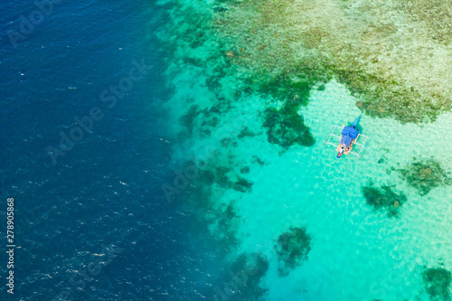 Staande foto Koraalriffen Boat on a coral reef. Sea surface with an atoll, coral reefs. Sea shoal and depth. Seascape with tourist boat.