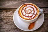 A cup of hot coffee with latte art on wooden table in day light
