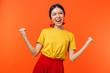 Leinwandbild Motiv Excited happy young woman posing isolated over orange wall background make winner gesture.
