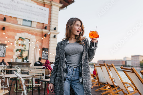 Blissful woman in casual attire raising glass with orange cocktail on city background Canvas Print