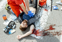 Ambluence Worker Applying Emergency Care To The Injured Bleeding Man Lying On The Pedestrian Crossing After The Road Accident