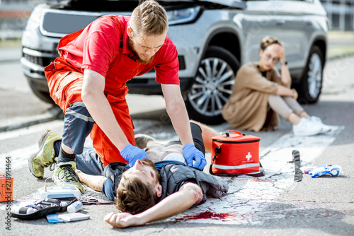 Ambluence worker applying emergency care to the injured bleeding man lying on th Canvas Print