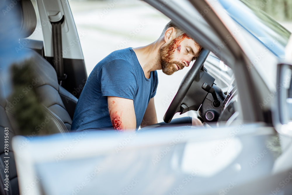 Fototapety, obrazy: Injured man with a broken head and bleeding wounds sitting on the driver seat without consciousness after the road accident inside the car