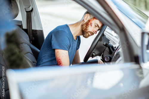Injured man with a broken head and bleeding wounds sitting on the driver seat wi Fototapet