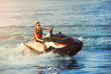 Young Adult Sporty Caucasian Woman Riding Jet Ski In Ocean Blue Water At Warm Evening Sunset. Beach Extreme Sport Activities And Recreation