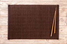 Two Sushi Chopsticks With Empty Bamboo Mat Or Wood Plate On Brown Wooden Background Top View With Copy Space. Empty Asian Food Background