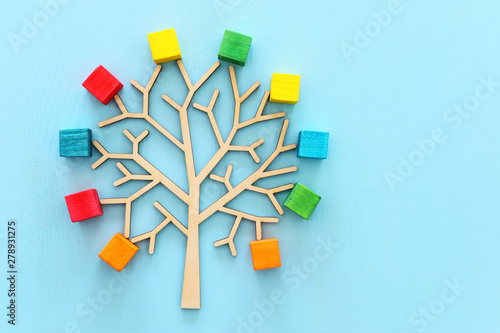 Obraz na plátně  Business image of wooden tree with colorful cubes over blue table, human resourc