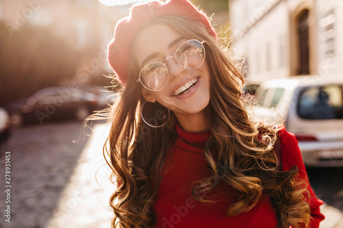 Close-up portrait of lovable french girl with elegant curly hairstyle looking to camera and laughing. Enthusiastic lovely lady in beret enjoying sunshine, walking on avenue.