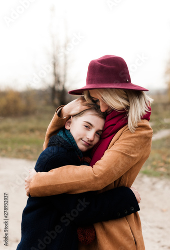Photo Young mother in a red hat hugs her son in the autumn forest..