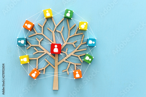 Business image of wooden tree with people icons over blue table, human resources Canvas Print