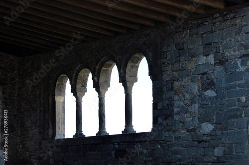 Vászonkép Finestra trifora con mura in pietra