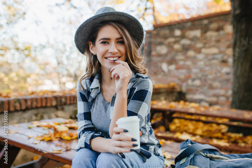 Fototapety, obrazy: Ecstatic white woman in casual shirt holding cup of tea on blur autumn background. Outdoor photo of interested european lady in hat with long black nails smiling in october weekend.