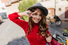 Close-up Portrait Of Inviting Blue-eyed Woman With Black Manicure Happy Smiling On Street Background. Amazing White Girl Wears Trendy Hat Posing With Peace Sign.