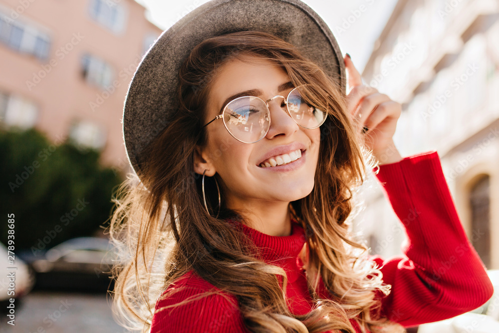 Fototapeta Close-up portrait of cheerful white woman in glasses touching her hat on blur background. Photo of fashionable girl with beautiful brown hair smiling to camera.