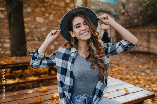 Fascinating european female model in casual checkered shirt posing with pleasure in yard in autumn. Dreamy white woman in hat enjoying september day.