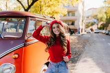 Inspired Young Caucasian Lady With Brown Hair Waving Hand, Walking Down The Street In Sunny Day. Outdoor Portrait Of Laughing White Girl In Knitted Clothes Posing Near Orange Bus.