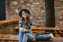 Lovable European Female Model Wears Casual Jeans And Blue Shirt Sitting Outdoor In Warm October Weekend. Stunning Young Woman Relaxing In Park In Autumn Day And Cute Smiling To Camera.