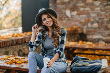 Interested Lady With Elegant Black Manicure Drinks Coffee On Wooden Bench With Golden Leaves On Background. Outdoor Portrait Of Gorgeous White Female Model Wears Hat And Casual Shirt Chilling In Park.