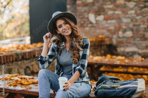 Fototapety, obrazy: Interested lady with elegant black manicure drinks coffee on wooden bench with golden leaves on background. Outdoor portrait of gorgeous white female model wears hat and casual shirt chilling in park.