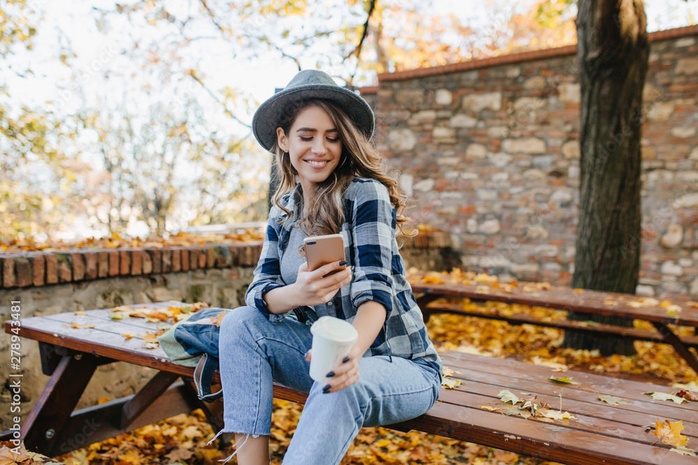 Fototapety, obrazy: Magnificent white woman wears casual clothes texting message in good september day. Outdoor portrait of pretty girl with sincere smile using phone while chilling in autumn yard.