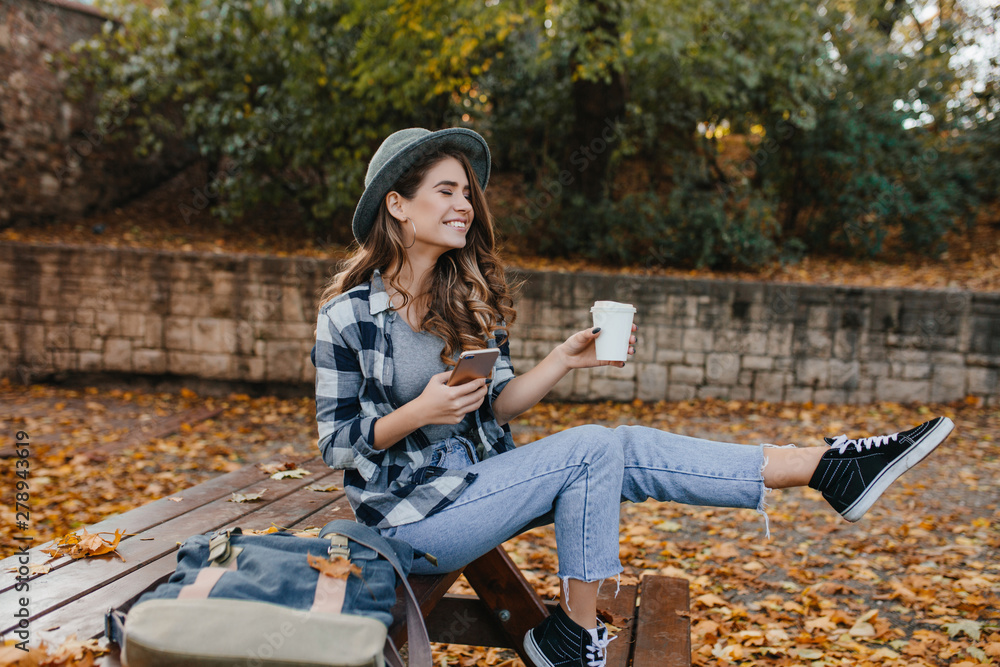 Fototapeta Carefree girl in vintage jeans fooling around in autumn park, holding phone. Enthusiastic european woman in trendy gray hat waving legs while posing with cup of coffee in yard.